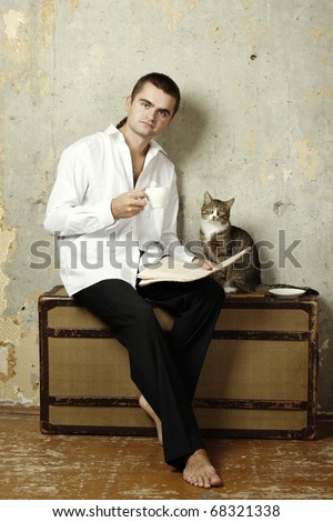Young man in a white shirt and trousers sitting on a suitcase drinks coffee and reads the newspaper, sitting next to a cat. Photo retro