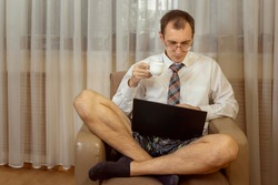 Young man in a white shirt with a tie and underwear works at a computer at home. Toned. Copy space