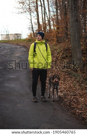 young man in a yellow jacket aged 20-24 on a walk with a Czech mustache, a hunting dog. Binary portrait of taking care of pet, love and relationship. Authentic situation on a walk. Dog walking. Foto stock ©