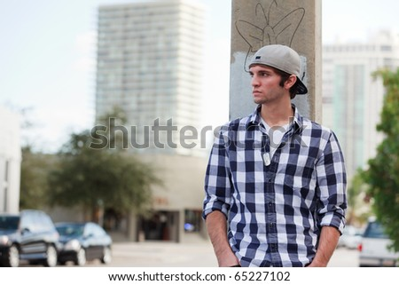 Young man in an urban lifestyle fashion pose leaning against a city utility pole wearing a hat.