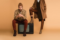 young man in autumn jacket and beanie sitting on vintage tv set near woman in stylish boots on beige background