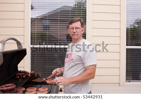 Young man in back yard barbecueing  hamburgers and sausages on a gas grill.