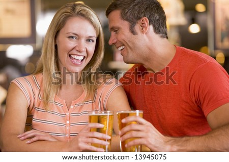 Young man in bar whispering into his girlfriends ear - stock photo
