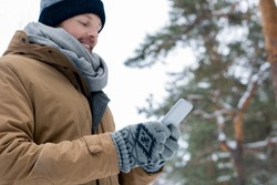 Young man in beanie, scarf, jacket and gloves scrolling in smartphone on winter day in snowbound forest
