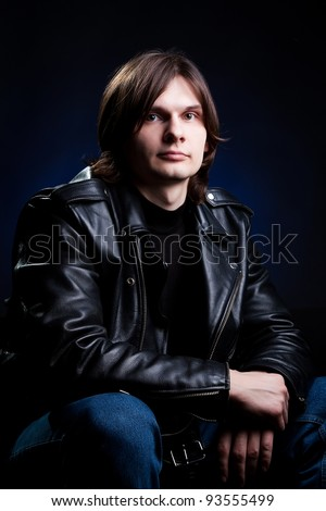 Young man in black leather jacket against dark background
