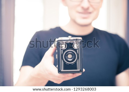 Young man in black shirt is taking a picture with a black german vintage camera