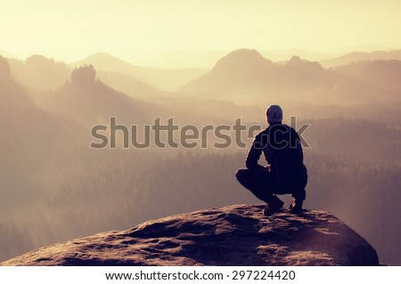 Young man in black sportswear is sitting on cliff's edge and looking to misty valley bellow. Autumn landscape. Foggy mountain.Person look. Man hike.Cliff edge. Climbing adventure.Guy look.Foggy valley