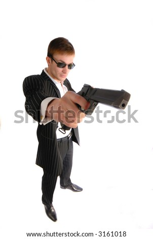 Young  man in  black suit with a pistol in  hand - stock photo