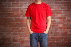 Young man in blank red t-shirt standing against brick wall, close up