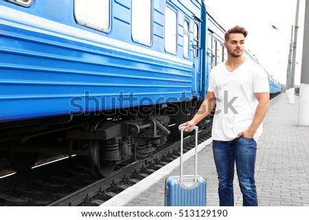 Young man in blank t-shirt with suitcase standing on railway platform near train