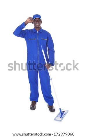 Young Man In Blue Boiler Suit Holding Mop Over White Background
