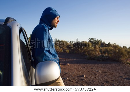 Young man in blue jacket and hood resting by his car, looking to the side and squinting in bright sunlight #590739224