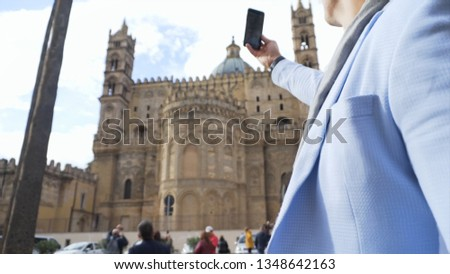 Young man in blue jacket taking picture with smartphone of the cathedral during vacation, tourism concept. Stock. A man makes a photo on the phone of the church in a sunny day.