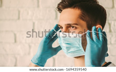 Young man in blue latex gloves putting on medical mask on face. Confident professional surgeon doctor in medical gloves on hands wearing protective face mask. Coronavirus COVID-19 personal protection