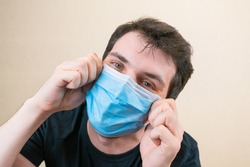 Young man in blue protective medical mask and happu with it. Self-isolation and quarantine. Stay home