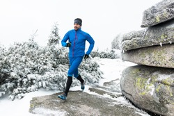 young man in blue sportswear running on the snow frozen trail in winter mountains with cold fog