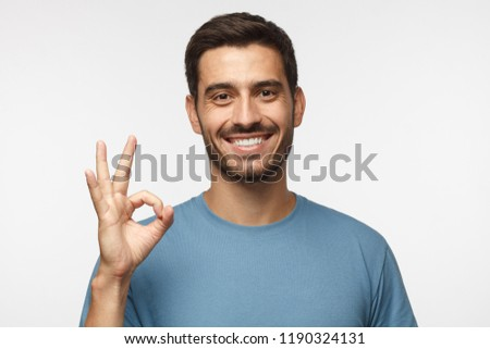 Young man in blue t-shirt having happy look, smiling, gesturing, showing OK sign. Caucasian male showing okay gesture with his fingers