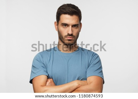 Young man in blue t-shirts tanding with arms crossed and serious concentrated face at camera, looking aggressive, isolated on gray background