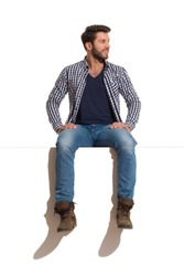 Young man in boots, jeans and unbuttoned lumberjack shirt is sitting on a top, smiling and looking away. Full length studio shot isolated on white.