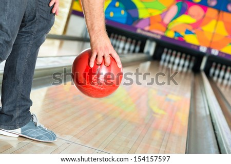 Young man in bowling alley having fun, the sporty man holding a bowling ball in front of the ten pin alley - stock photo