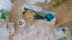 Young Man in Brown Jumper and Grey Jeans Lying Down on a Sofa, Using a Laptop. He is Happy and Smiles. Cozy Living Room with Modern Interior with Plants, Table and Wooden Floor. Top View.