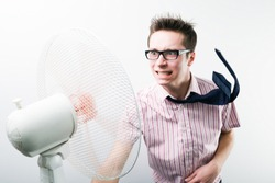 Young man in business casual clothing in glasses feeling stressed over fan with air flow to his face over white background in photo studio. Smart casual style and business situations