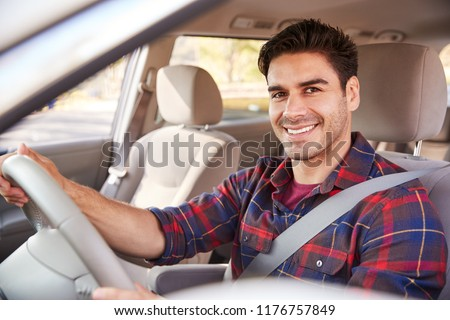 Young man in car driving seat looking to camera, portrait