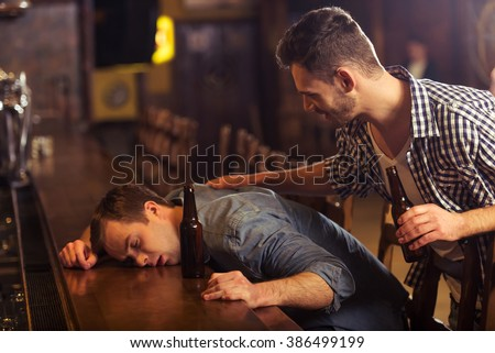 Young man in casual clothes is sleeping near the bottle of beer on a bar counter in pub, another man is waking him up #386499199