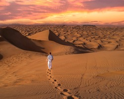 Young man in casual clothes walking in the Dubai desert during sunset