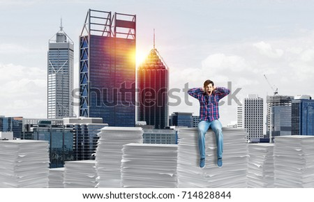 Young man in casual clothing sitting on pile of documents with cityscape and sunlight on background. Mixed media. #714828844