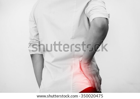 Young man in casual office shirt having hip pain (Selective Focus)