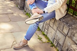 Young man in casual summer clothes in light beige suede leather shoes with laces sitting on the parapet in the park. Men's fashion, style, fashion trends.
