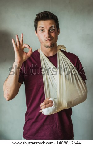 Young man in causal clothes with plaster on his arm or wrist, stitches and patches above his eye, maintaing a good and happy spirit, showing an OK sign with his good hand. Stok fotoğraf ©