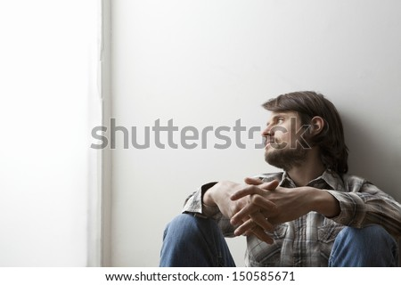 Young man in checked shirt siting with hands clasped against a wall #150585671