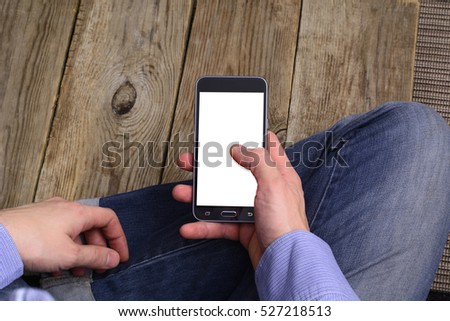 Young man in checkered blue shirt is holding phone with white screen on right hand. #527218513