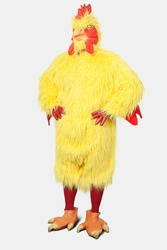 Young man in chicken suit standing with hands on hips against gray background