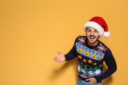 Young man in Christmas sweater and hat on color background. Space for text
