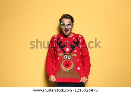 Young man in Christmas sweater with party glasses on color background - Shutterstock ID 1215026473