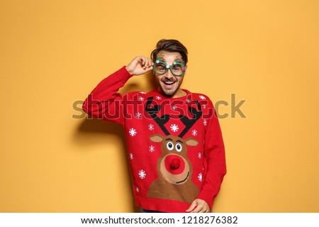 Young man in Christmas sweater with party glasses on color background - Shutterstock ID 1218276382
