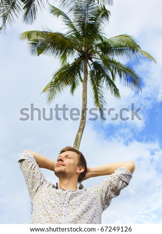 Young man in colorful shirt resting under a palm tree