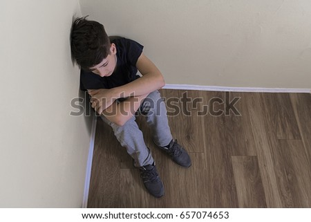 Young man in depression. Sad teenager boy. Sad depressed boy in an empty room. stressed out male teenager. Negative human emotion. Young people and emotions concept. teen depression, pain, suffering.  #657074653