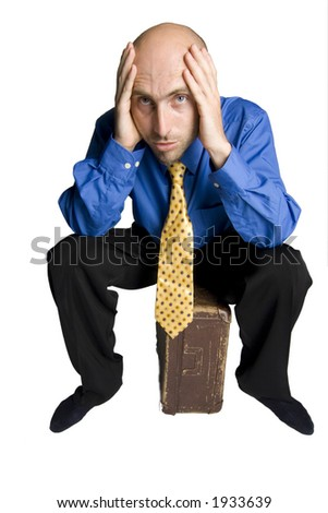 Young man in depression sitting on his suitcase - stock photo