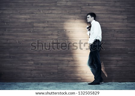 Young man in depression standing against a wall