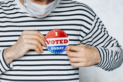 young man in face medical mask wearing on shirt I VOTED TODAY pin. election day on coronavirus pandemic. November elections in the United States 2020. Copy Space. blurred background. New normal