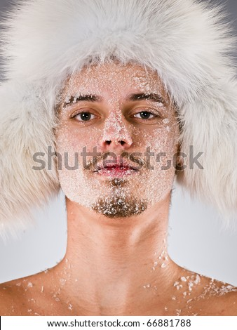 Young man in fur cap with which face covered with hoarfrost