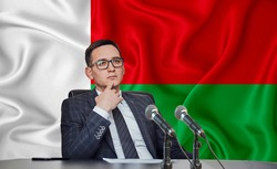 Young man in glasses and a jacket at an international meeting or press conference negotiations, on the background of the flag Madagascar