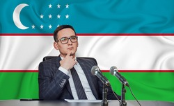 Young man in glasses and a jacket at an international meeting or press conference negotiations, on the background of the flag Uzbekistan, Tashkent, Uzbek