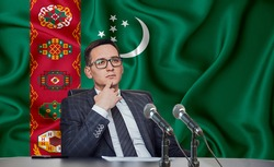 Young man in glasses and a jacket at an international meeting or press conference negotiations, on the background of the flag turkmenistan