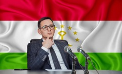 Young man in glasses and a jacket at an international meeting or press conference negotiations, on the background of the flag Tajikistan