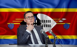 Young man in glasses and a jacket at an international meeting or press conference negotiations, on the background of the flag swaziland